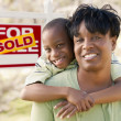 Mother and Child In Front of Sold Real Estate Sign - Stock Photo