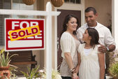 Hispanic Family in Front of Home with Sold Real Estate Sign — Stock Photo