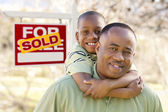 Father and Son In Front of Sold Real Estate Sign — Stock Photo