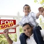hispânico pai e filho com sinal de imóveis vendidos — Foto Stock