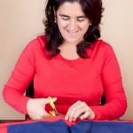 Hispanic woman cutting a piece of fabric — Stock Photo #10424961