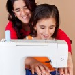 Mother and daughter sewing together — Stock Photo