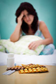 Pills and out of focus sick or depressed woman — Stock Photo