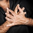 Close up of two hands grabbing a chest - Stock Photo