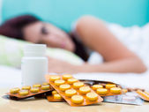 Sick woman in bed and pills from her medical treatment — Stock Photo