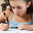 Beautiful hispanic girl working on her school project at home — Stock fotografie #8481437