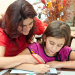 Latin mother helping her daughter with her school art project — Stock Photo