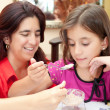 Hispanic mother and daughter sharing a homemade chocolate dessert — Stock Photo #8481803