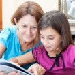 Latin grandmother and girl reading a book at home — Stock Photo #8481821
