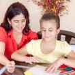 Latin mother helping her daughter with her school art project — Stock Photo #8481824