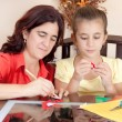 Latin mother helping her daughter with her school art project — Stock Photo #8481827