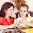 Latin mother helping her daughter with her school art project - Stock Photo