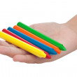 Child hand with a group of color crayons isolated on white — Stock Photo
