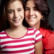 Hispanic mother and daughter on a dark background — Stock Photo