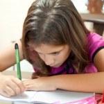 Small hispanic girl working on her homework — Stock Photo