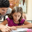 Young latin gather helping her daughter with homework — Stock Photo #8482026
