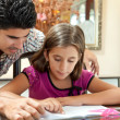 Young latin gather helping her daughter with homework — Stock Photo