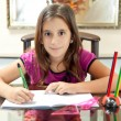 Foto de Stock  : Small hispanic girl working on her homework
