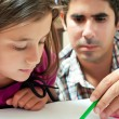 Small hispanic girl and her young father working on a school project - Stock Photo