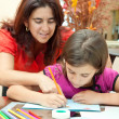 Young latin mother helping her daughter with her art project — Stock Photo #8482070