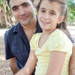 Hispanic father with her small daughter in a park — Stock Photo