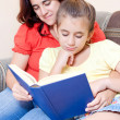 Latin girl and her mother reading a book at home — Foto Stock