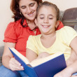 Latin girl and her mother reading a book at home — Foto de Stock