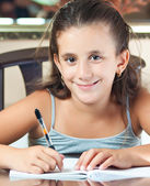 Beautiful hispanic girl working on her school project at home — Stockfoto