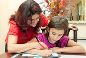 Latin mother helping her daughter with her school art project — Stockfoto