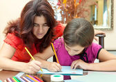 Latin mother helping her daughter with her school art project — Stock fotografie
