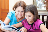 Latin grandmother and girl reading a book at home — Stock Photo