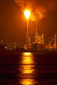 Oil refinery at night with a huge smike column polluting the air — Stock Photo