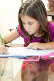 Small hispanic girl working on her homework — Stok fotoğraf