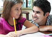 Young latin gather helping her daughter with homework — Stok fotoğraf