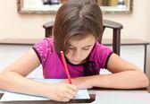 Pequena garota hispânica, trabalhando em seu projeto de escola em casa — Fotografia Stock