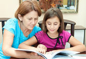 Hispanic grandmother rading with her granddaughter at home — Stock Photo