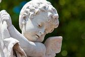 Cabeza de un pequeño ángel con un fondo verde difuso — Foto de Stock