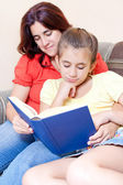 Latin girl and her mother reading a book at home — Stock Photo