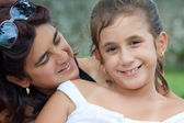 Beautiful young hispanic mother with her daughter in a park — Stock Photo