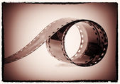 Photographic film reel on a vintage sepia background — Stock Photo