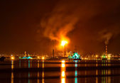 Oil refinery at night with a huge smoke column polluting the air — Stockfoto