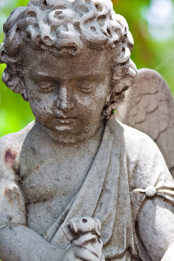 Old statue of an infant angel with a diffused green vegetation background — Stock Photo #8482288