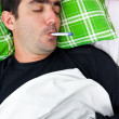 Sick hispanic man laying in bed with a thermometer — Stock Photo #8779981
