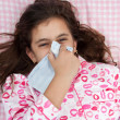 Hspanic girl sick with the flu and sneezing — Stock Photo