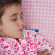Sick hispanic girl with a thermometer in her mouth — Stock Photo