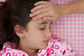 Hispanic girl sick with fever laying in bed — Stock Photo