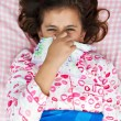 Hispanic girl sick with the flu laying in her bed — Stock Photo
