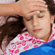 Stock Photo: Hispanic girl sick with fever laying in her bed