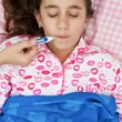 Hispanic girl sick with fever laying in her bed — Stock Photo #8822468