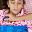 Hispanic girl sick with fever laying in her bed — Stock Photo